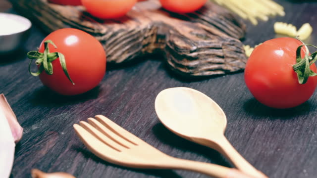 Uncooked pasta and tomato Red cherry tomatoes, spoon and fork with spices and uncooked pasta on dark wood cutting board and on black table. Close-up uncooked pasta stock videos & royalty-free footage