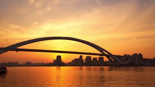 sotto il cielo dorato al tramonto, colpo di traffico time-lapse sul ponte shanghai lupu - grandangolo composizione cinematografica video stock e b–roll