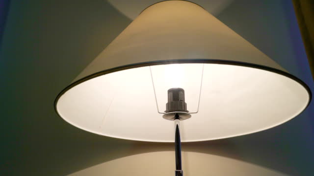 Under the hat of the lampshade in the bedroom Under the hat of the lampshade in the bedroom with the bulb turned on lamp shade stock videos & royalty-free footage