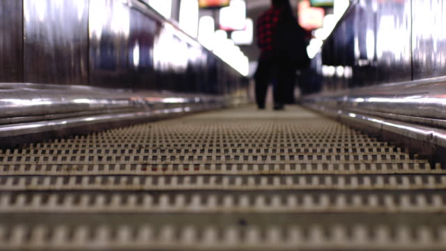 Underground escalators at rush hour. Blurred background with bokeh lights. 3840x2160, FullHD video
