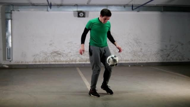 underground parking. a young deft soccer man training football tricks - acrobazia video stock e b–roll