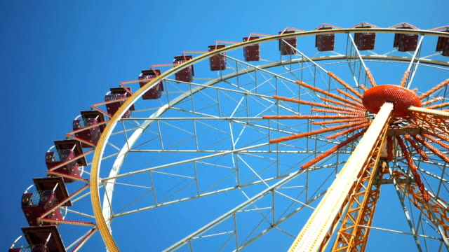 Underside view of a ferris wheel over blue sky. Ferris wheel at amusement park video