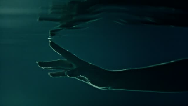 Underwater meditation. Reaching hand reflections Young woman floating underwater. Light flares touching stock videos & royalty-free footage