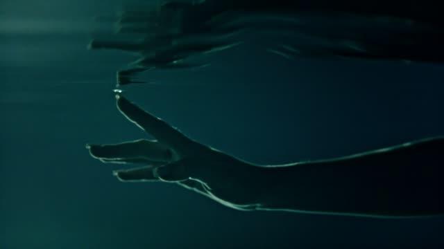 underwater meditation. reaching hand reflections - mindfulness стоковые видео и кадры b-roll