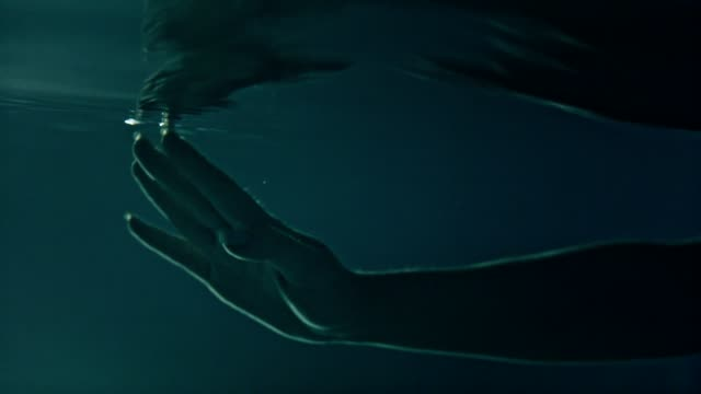 Underwater meditation. Reaching hand reflections