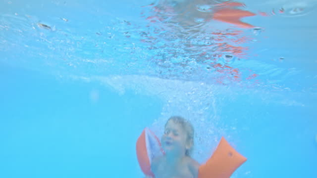 TD Underwater shot of a boy with swimmies jumping into the pool video