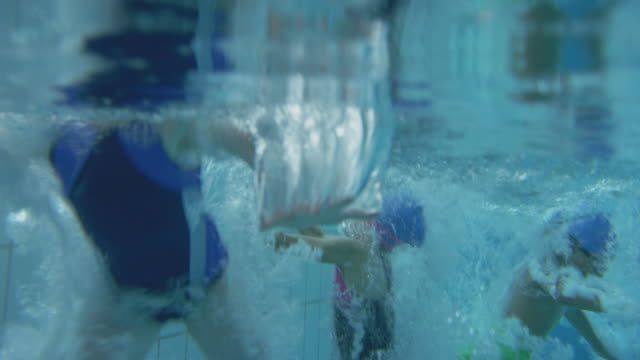 Underwater Shot Of Children Jumping Into Indoor Swimming Pool From Edge