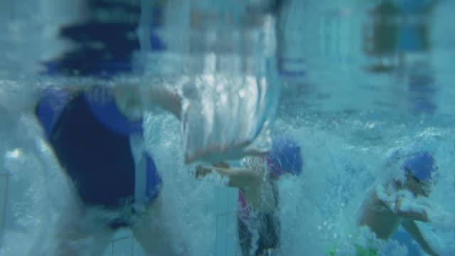 vídeos de stock e filmes b-roll de underwater shot of children jumping into indoor swimming pool from edge - nadar