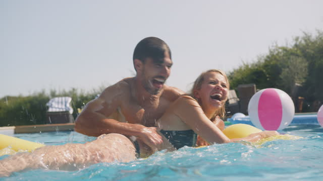 Underwater Shot Of Man Surprising Woman Floating On Airbed In Swimming Pool On Summer Vacation video