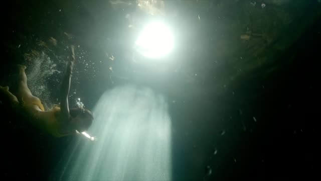 vídeos de stock e filmes b-roll de underwater shot of woman diving in cenote in mexico, sunbeam coming from cave hole. - cisterna água parada