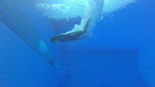 LD Underwater view of a female diving athlete landing in the pool
