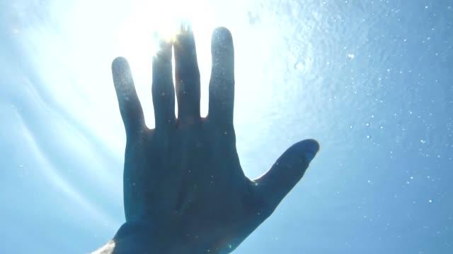 underwater view of hand in sun rays shining - погружённый стоковые видео и кадры b-roll