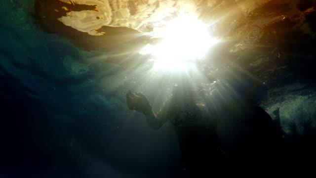 undervattens bild av mor och son lärande simma med uppblåsbara gummi ring mot solnedgången solen skiner strålar - inflatable ring bildbanksvideor och videomaterial från bakom kulisserna