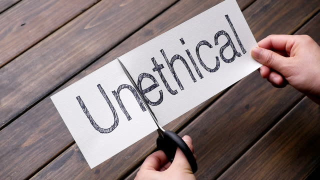 unethical to ethical by scissors on pattern wood plank woman's beautiful hands cut paper by scissors on pattern wood plank morality stock videos & royalty-free footage