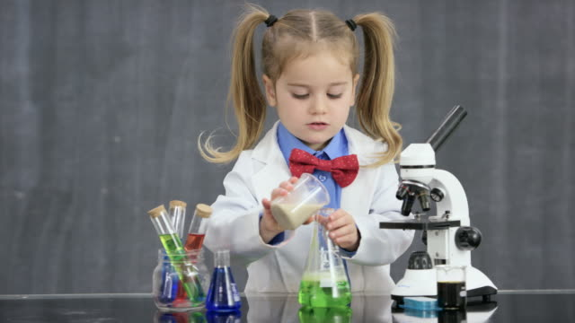Unexpected Results A preschool aged girl dressed in a bowtie and lab coat stands behind a table with scientific instruments - flasks, beakers, and a microscope.  genius stock videos & royalty-free footage