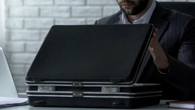 Unfair accountant stealing money from briefcase, embezzlement of company budget video