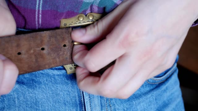 unfastening the belt on trousers, decorative buckle