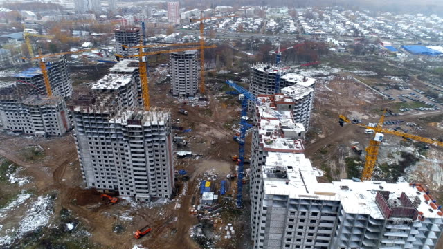 Unfinished apartment buildings covered by snow. video