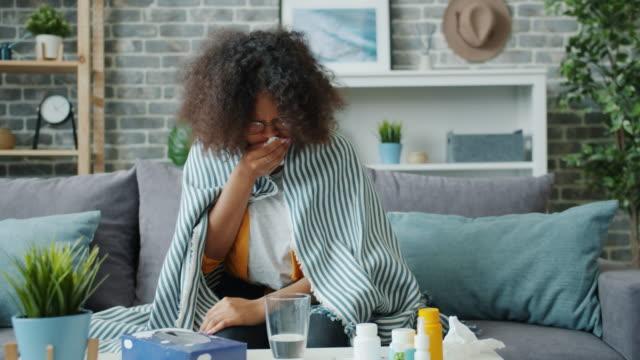 不高興的非洲裔美國婦女咳嗽在紙巾感覺生病在家裡 - 季節 個影片檔及 b 捲影像