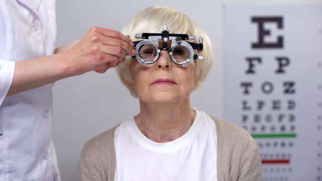 vidéos et rushes de femme âgée malheureuse dans les yeux serrants de réfractaire et secouant la tête, mauvais diopter - réfracteur