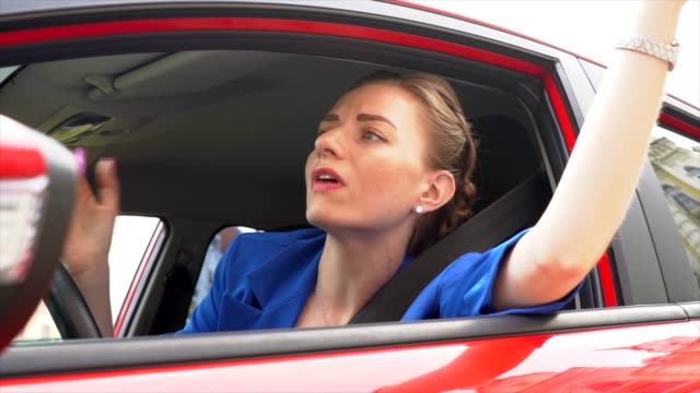 unhappy and maad young woman got stuck on traffic. she screams. woman get loudspeaker and speak in it. then she put it away and drive. - ingorgo stradale video stock e b–roll