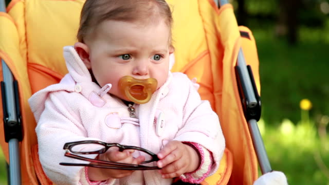 Unhappy baby holding the eyeglasses in her hands video