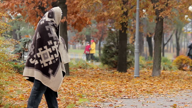 Unhappy beggar limping in autumn park, social vulnerability and poverty problem video