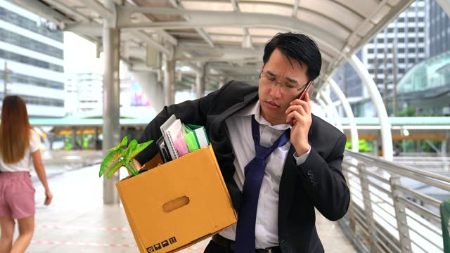 vídeos de stock e filmes b-roll de unhappy businessman talking with mobile phone and carrying his belongings in a paper box after being fired. - ser despedido