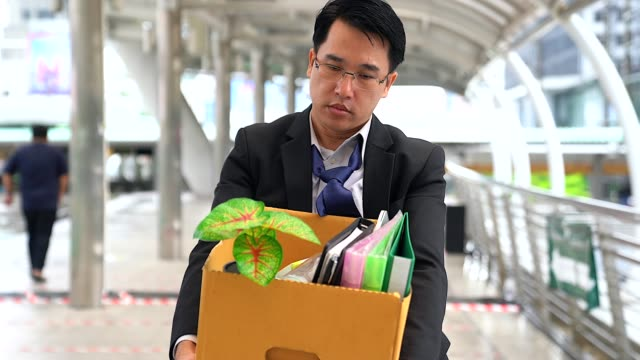 Unhappy businessman walking and carrying his belongings in a paper box after being fired.