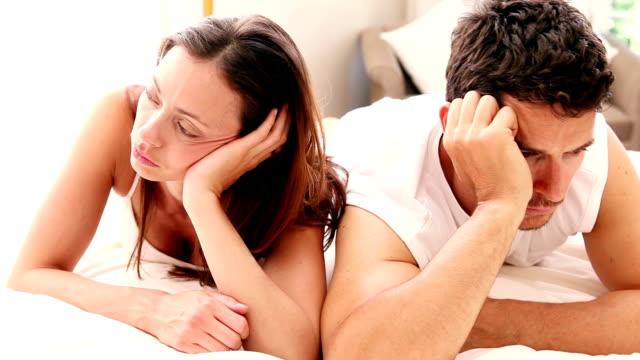 niezadowolony para leżąc na łóżku nie mówić - 30 39 lat filmów i materiałów b-roll