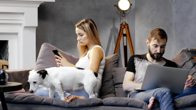 Unhappy couple quarreled and sitting in different directions on sofa with dog video