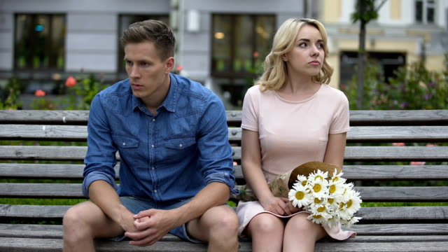 unhappy couple sitting after fight, girl leaving and throwing flowers on bench - chiedere scusa video stock e b–roll