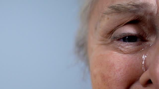 vídeos y material grabado en eventos de stock de llorando triste arrugada senior femenina mirando a cámara, media cara closeup - llorar