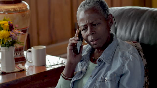 Unhappy elderly black woman talking on her mobile phone shaking her head no