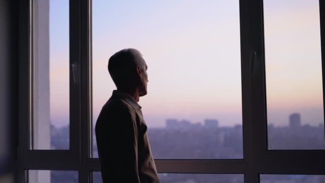 Unhappy elderly man looking in window, feeling lonely in city, sad memories