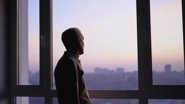 unglücklicher älterer mann, der ins fenster schaut, sich einsam in der stadt fühlt, traurige erinnerungen - introspektion stock-videos und b-roll-filmmaterial