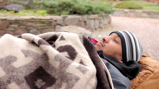 Unhappy homeless man sleeping in city street, socially vulnerable poor person video