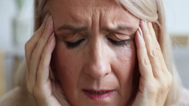 Unhappy Ill mature female retiree having head painful feelings.