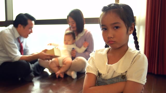 unhappy jealous little girl with her family in the background. - rivalità video stock e b–roll