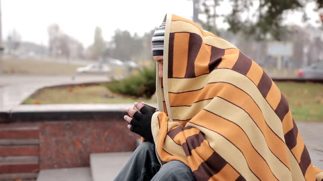 Unhappy male bum sitting alone in cold street, warming with coffee and blanket video