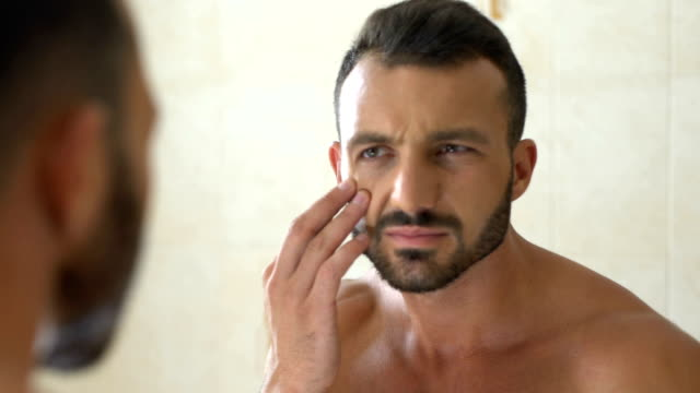 Unhappy man checking wrinkles on face in front of mirror in bathroom, aging