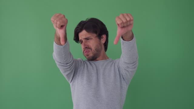 vídeos y material grabado en eventos de stock de hombre infeliz dando pulgares hacia abajo gesto - moda playera