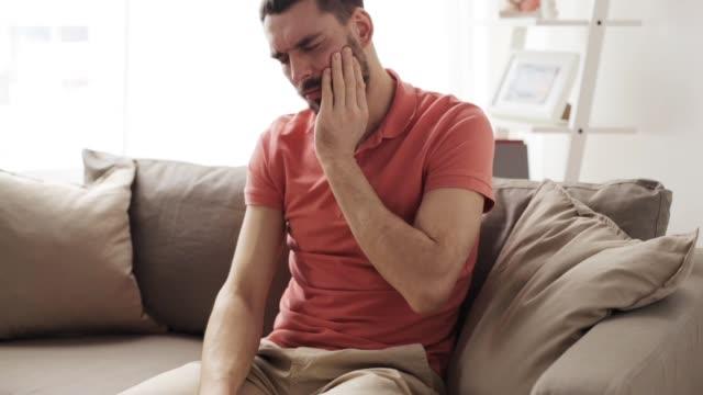 unhappy man suffering toothache at home - bevanda calda video stock e b–roll
