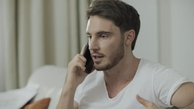 Unhappy man talking mobile phone at home. Angry person scream at phone