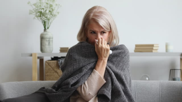 Unhappy middle aged female retiree suffering from flu cold. Covered in plaid unhealthy older mature woman sneezing, wiping runny nose, sitting alone at home. Unhappy middle aged female retiree suffering from flu cold allergic reaction, healthcare concept. shivering stock videos & royalty-free footage