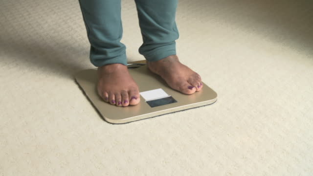 Unhappy Overweight Woman Weighing Herself On Scales video
