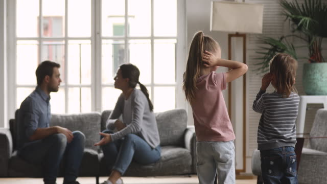 Unhappy parents arguing fighting while sad innocent children closing ears