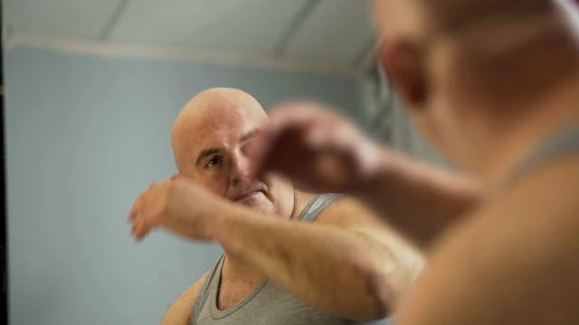 unglücklich plump männlich sein spiegelbild betrachten und nachdenken über probleme - kräftig gebaut stock-videos und b-roll-filmmaterial