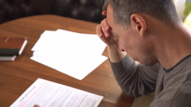 Unhappy sad man reading letter, bill, bank statement paper or tax document
