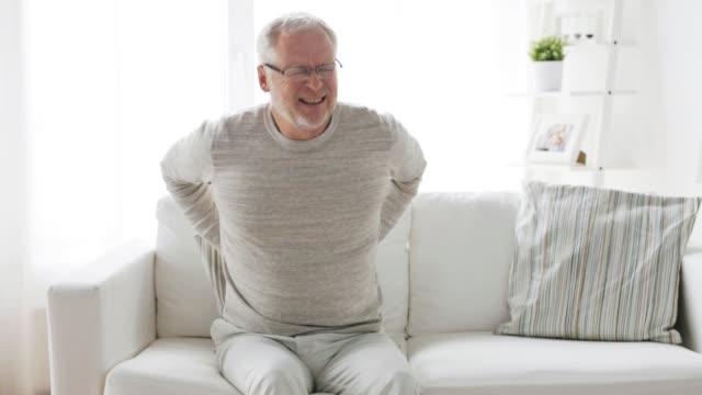 unhappy senior man suffering from backache at home - dorsale video stock e b–roll